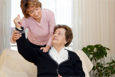 caregiver massaging elderly woman's arm